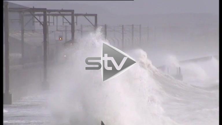 Waves Crashing Over Sea Wall and Train